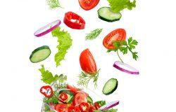 与蔬菜一起飞行的玻璃沙拉碗:番茄、胡椒、黄瓜、洋葱、小茴香和欧芹。孤立于白色背景