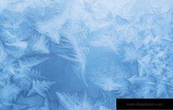 窗户玻璃上明亮的蓝色霜冻图案(作为抽象的冬季背景)